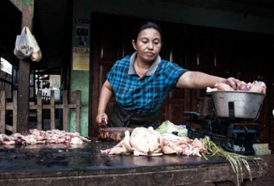 A butcher at work in a marketplace on Sumbawa Island, Indonesia.