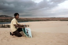 A worker waits to rent mats to tourists at the sand dunes outside Mui Ne, Vietnam.