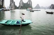 A woman paddles a fishing boat in Halong Bay, Vietnam