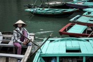 A woman sits in a fishing boat in Halong Bay, Vietnam.